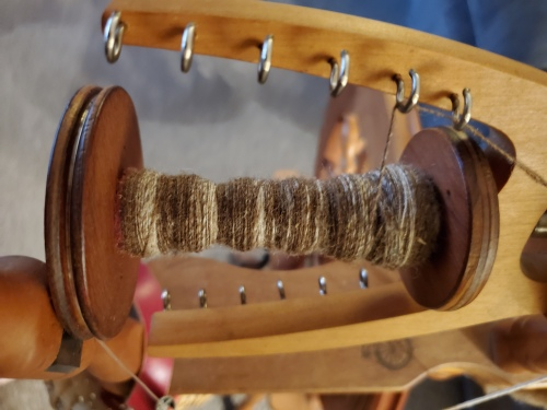 A brown single on a bobbin on a spinning wheel