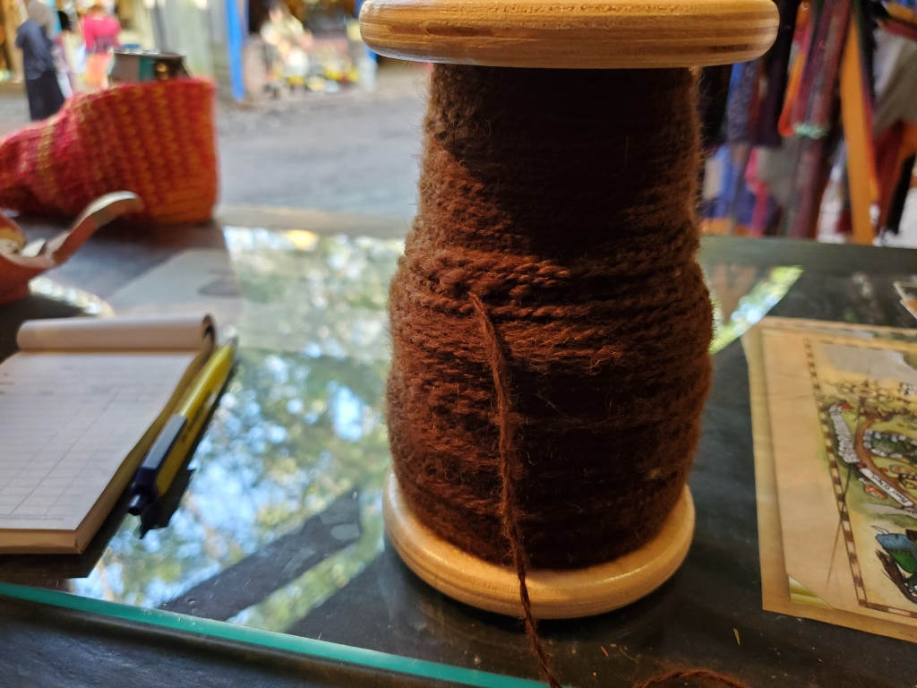 A bobbin of plied alpaca in the booth