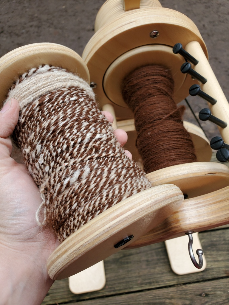 A bobbin of plied alpaca and half a bobbin of alpaca single on the demo platform
