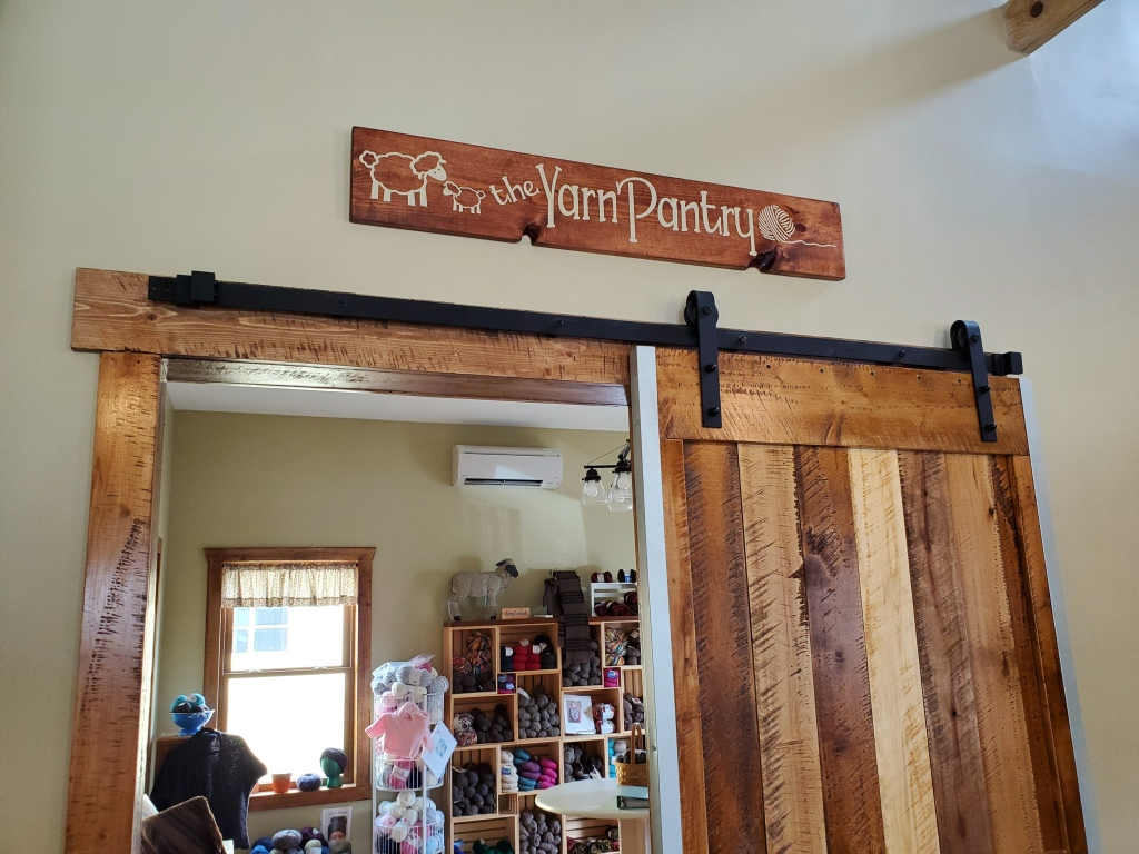 "Sign that says ""The Yarn Pantry"" over a barn door"