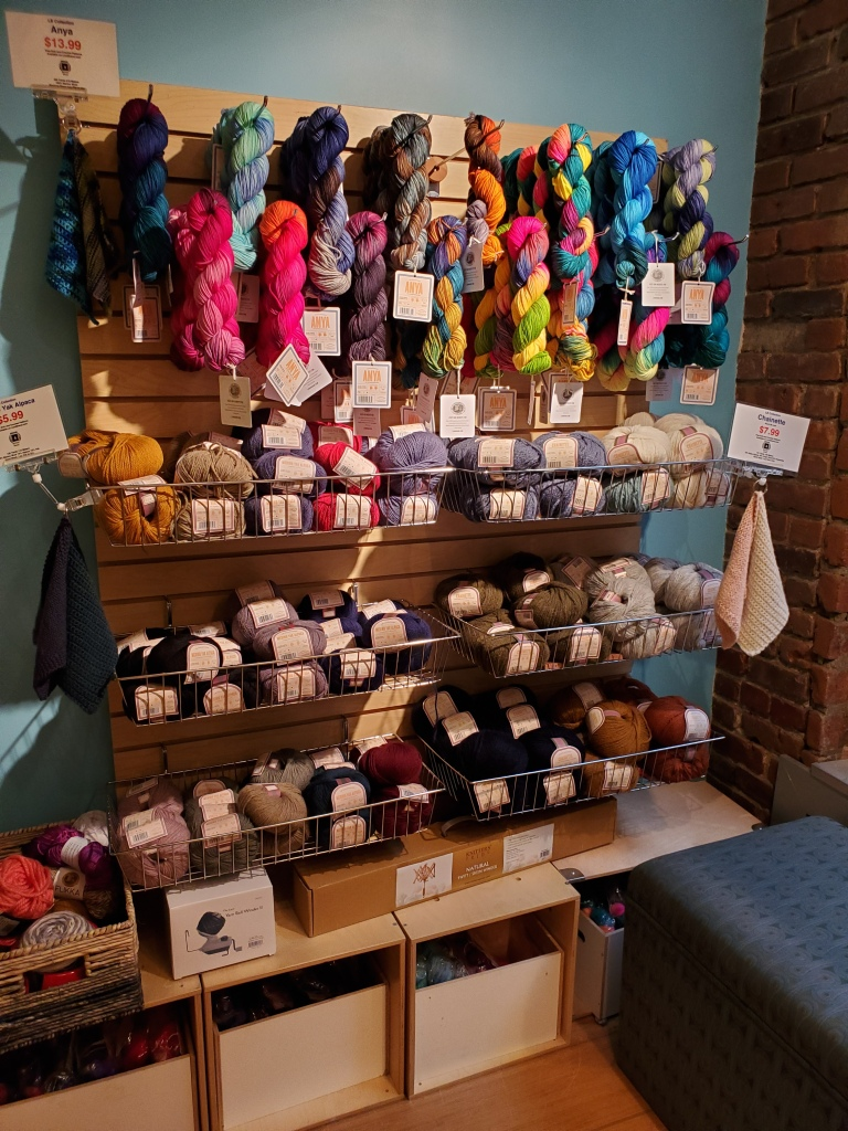 Wall of sale yarns in the Lion Brand Studio