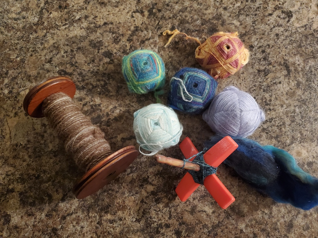 A bobbin half full of a tweedy brown yarn, five Turkish turtles in assorted colors, and a Turkish drop spindle.
