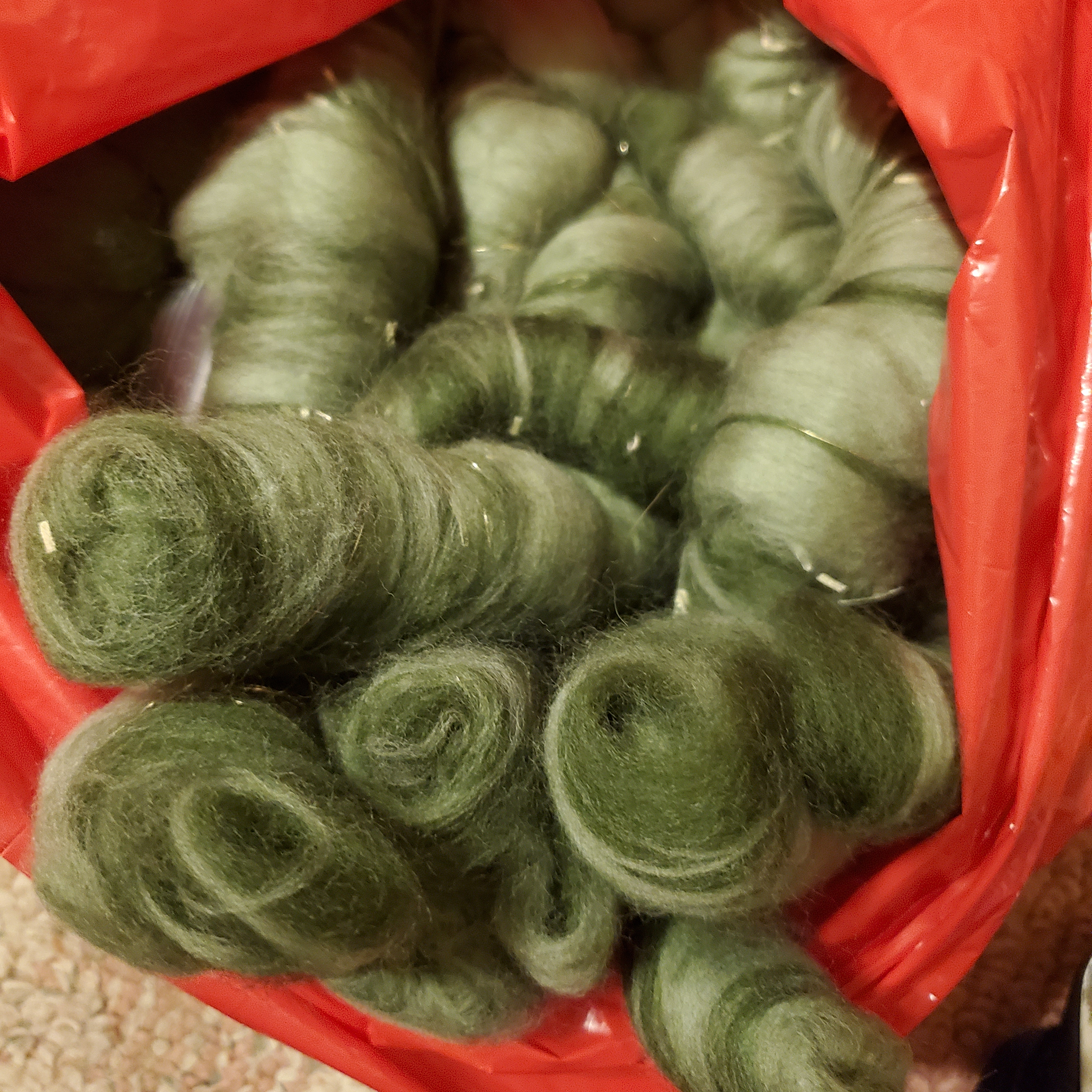 Green art-yarn rolags in a plastic bag.
