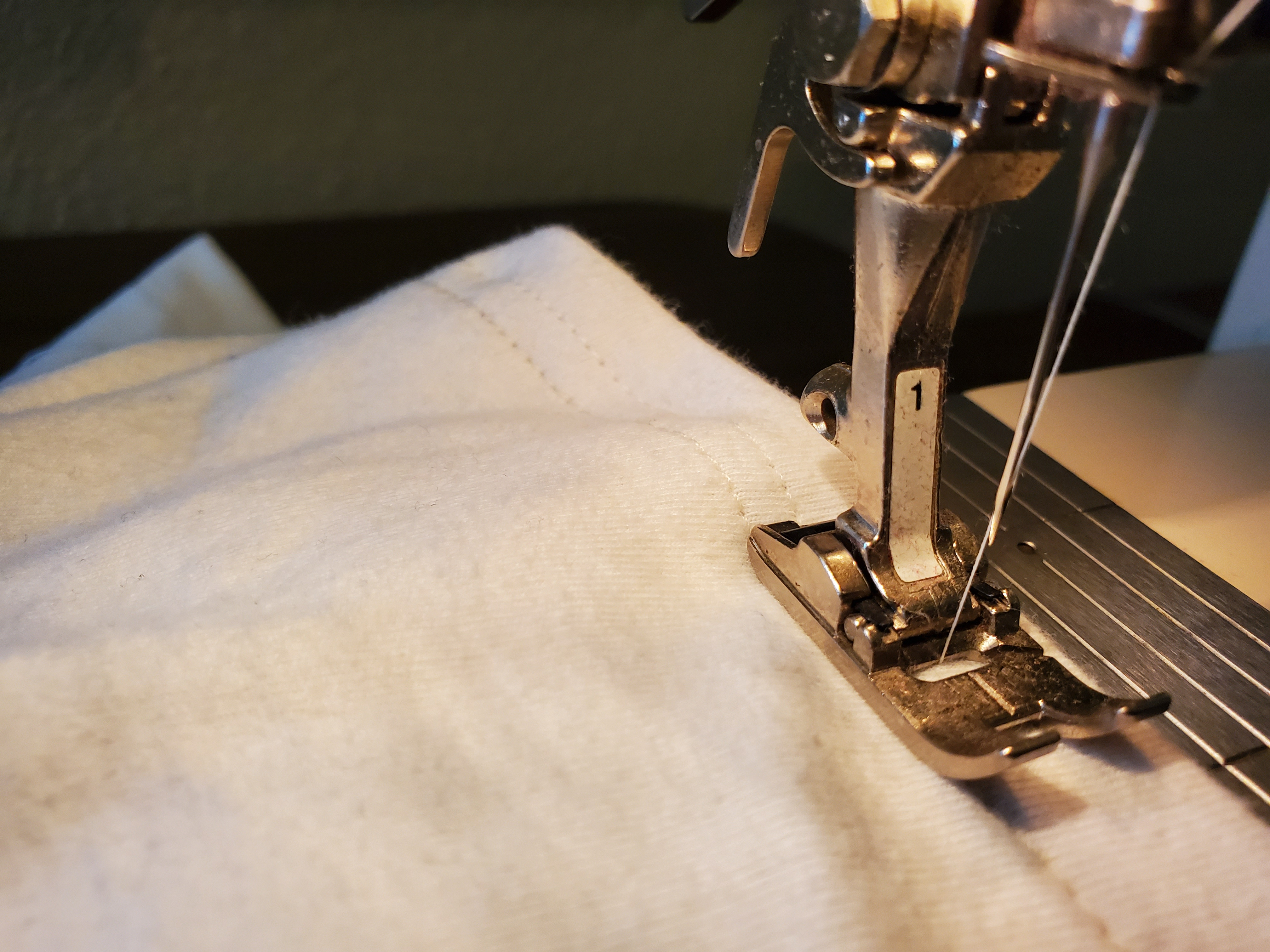 sewing machine needle and pressure foot on shirt, the second stitch line is visible