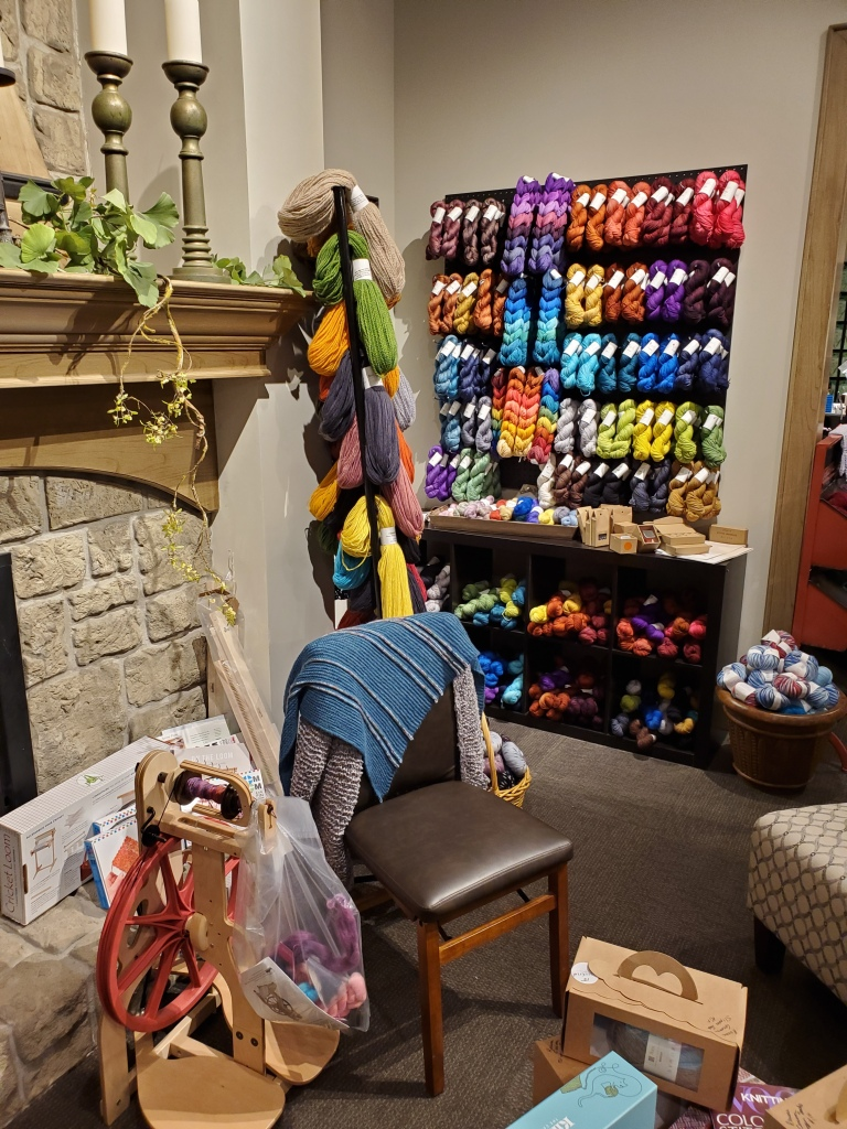 A wall of yarn and a spinning wheel