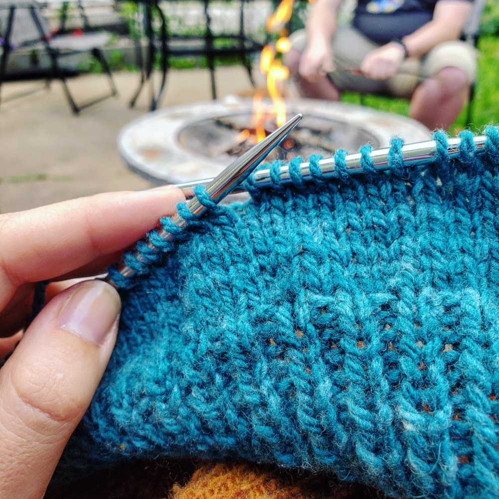 Blue knitting project in front of a fire