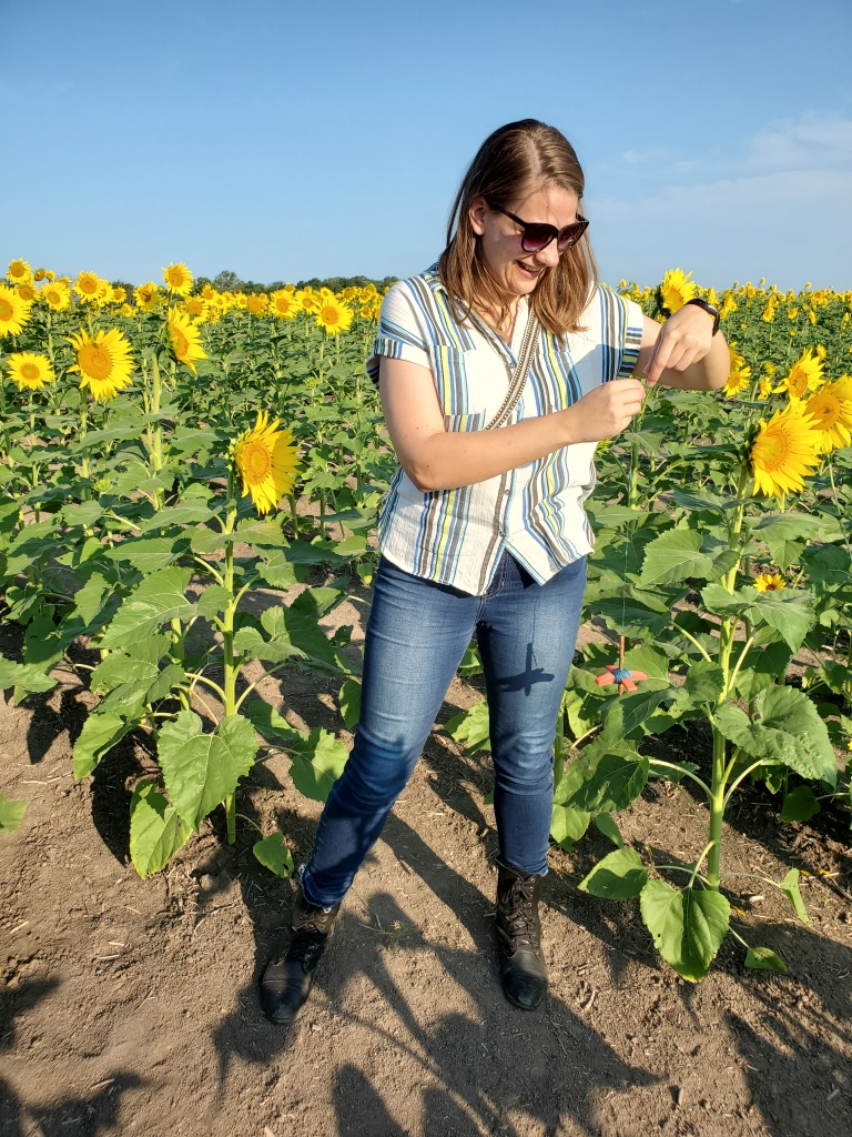 Emma spinning on a spindle in a field of sunflowers