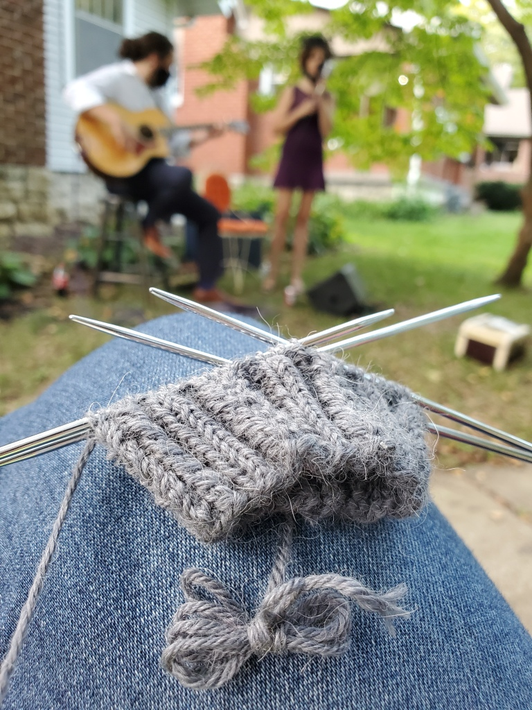 A grey sock cuff with an out-of-focus jazz duo in the background