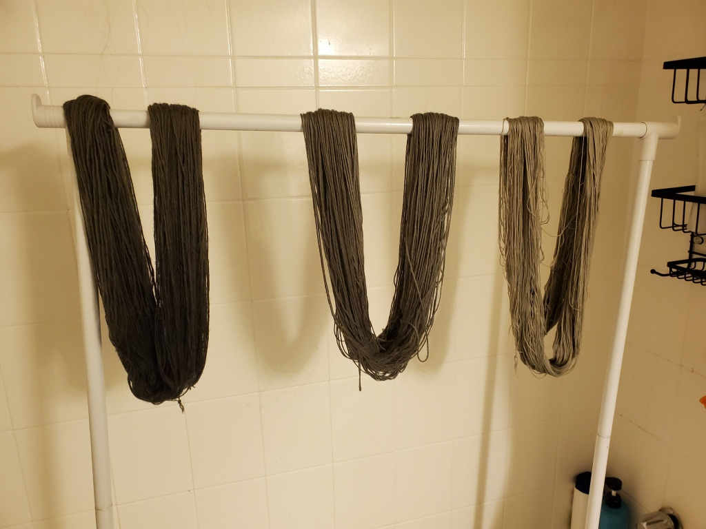 three skeins in various shades of gray