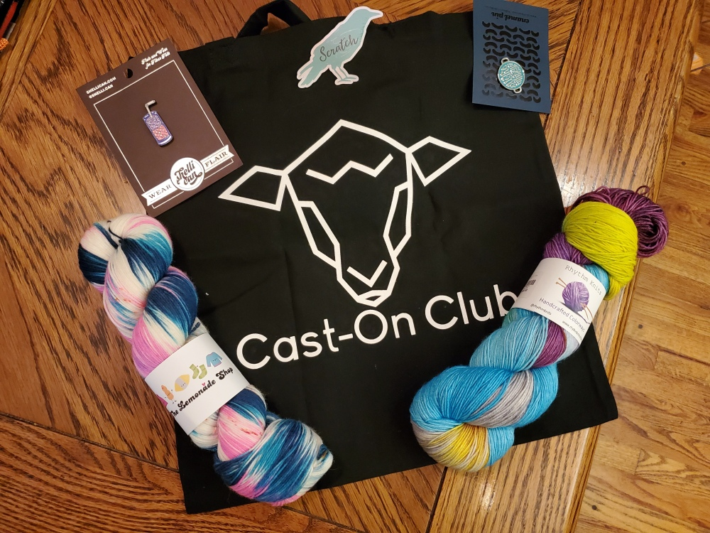 "Two hand-dyed skeins of yarn, Two enamel pins, a ""Scratch Supply Co."" sticker, and a black project bag that reads ""Cast-On Club"""