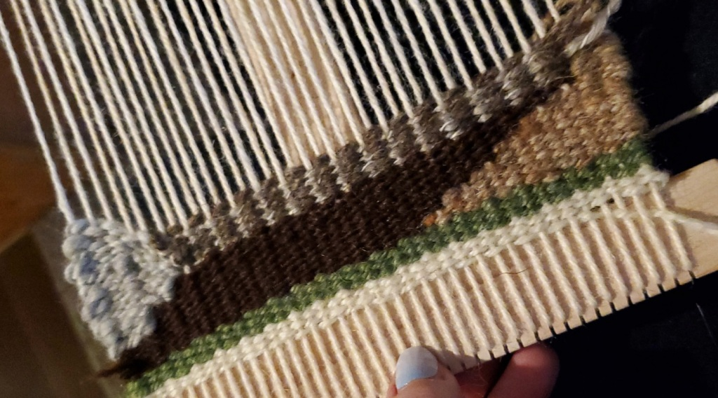 the start of a tapestry weaving in green and brown wools