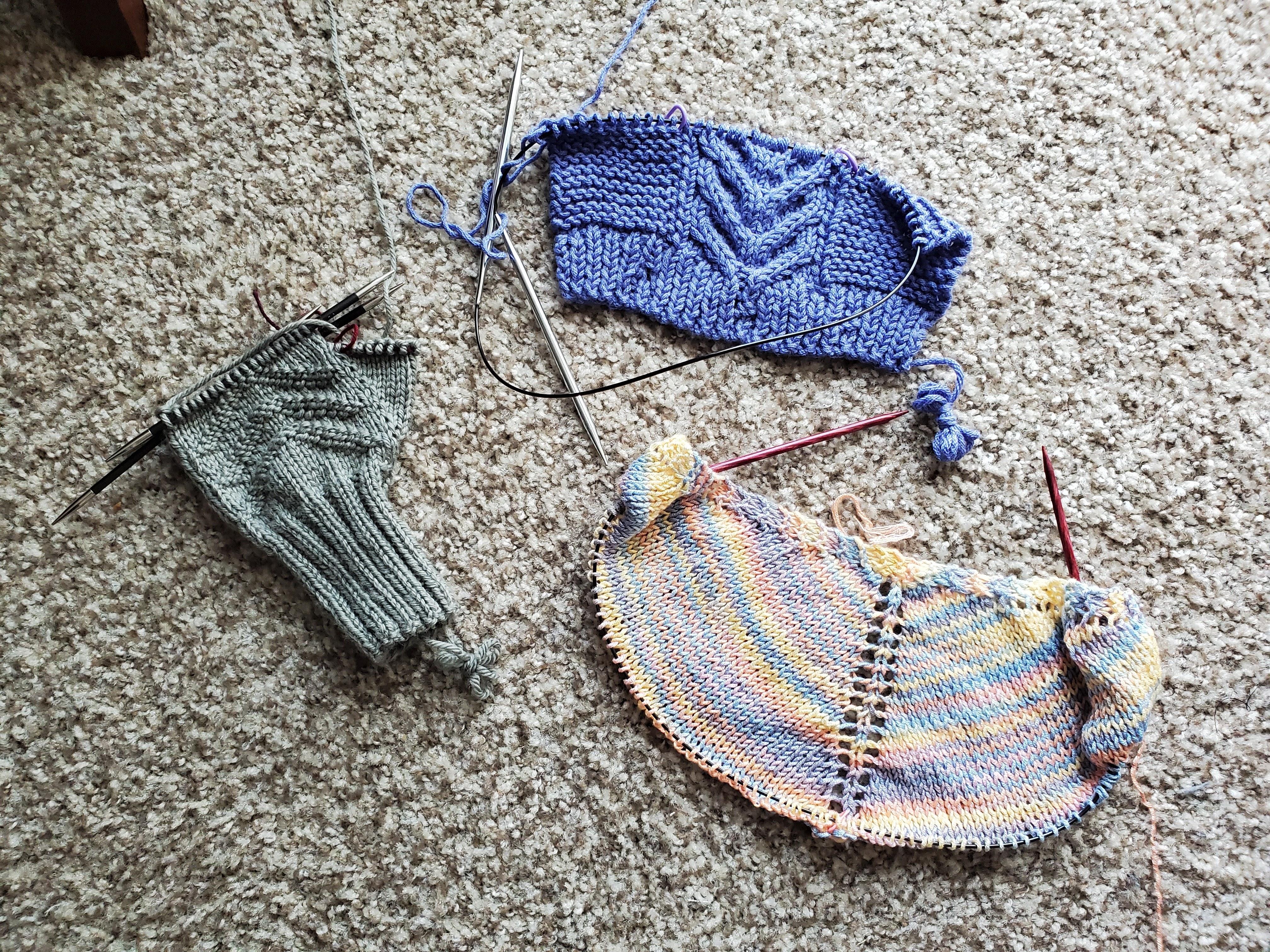 three in-progress knitting projects