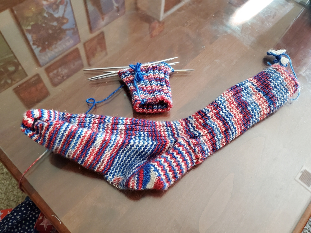 A finished and a just started red, white, and blue sock