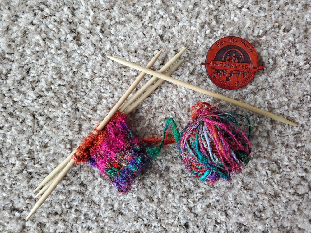 """Rainbow, in-progress knitting project with a button that says """"Vaccinated for the good of the realm"""""""